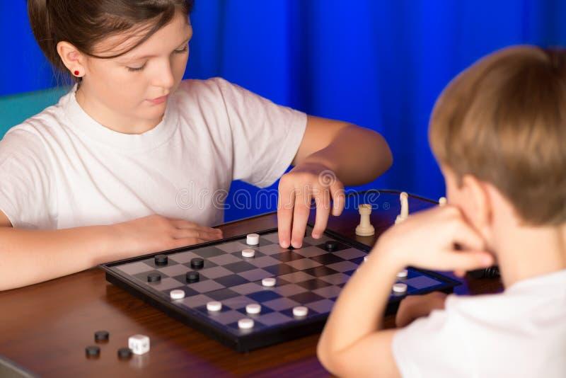 Kinderenjongen en meisje die een raadsspel genoemd spelen Controleurs stock foto's