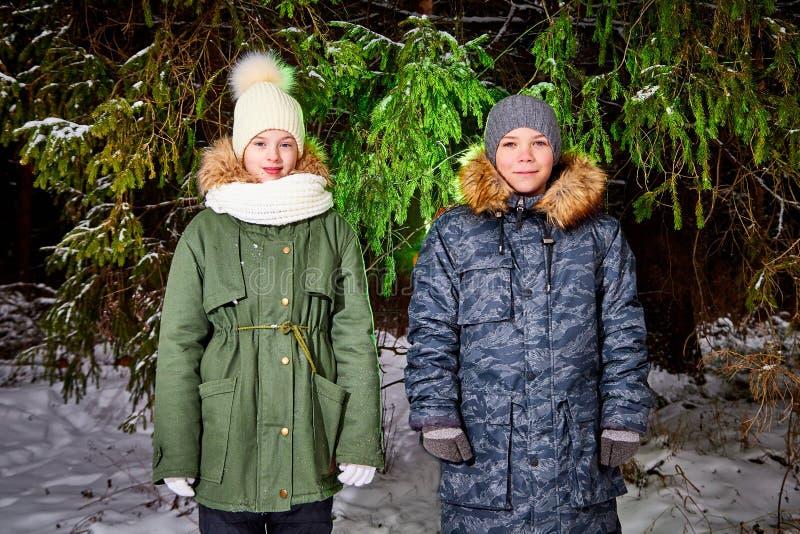 Kinderenjongen en meisje die in sneeuwbos lopen in een de winterdag Tieners die reis en rust in weekend hebben openlucht stock afbeeldingen