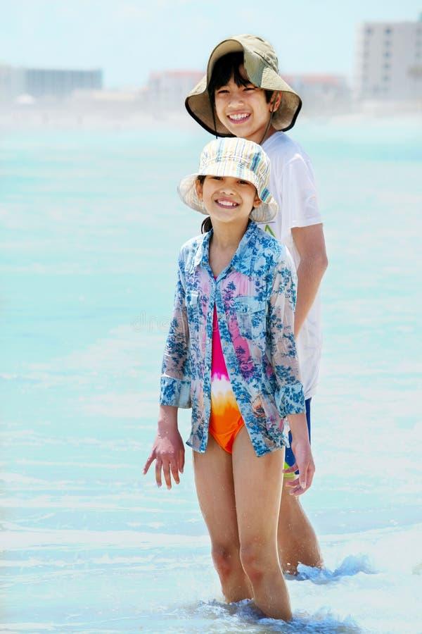 Kinderenknie diep in oceaangolven stock fotografie