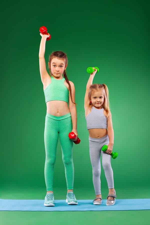 Kinderenmeisjes die geschiktheidsoefeningen op groene achtergrond samen doen royalty-vrije stock foto