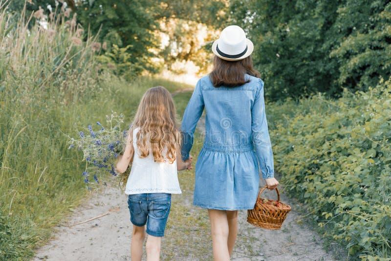 Kinderenmeisjes op de handen van de boswegholding Zonnige de zomerdag, de mand van de meisjesholding met bessen stock foto