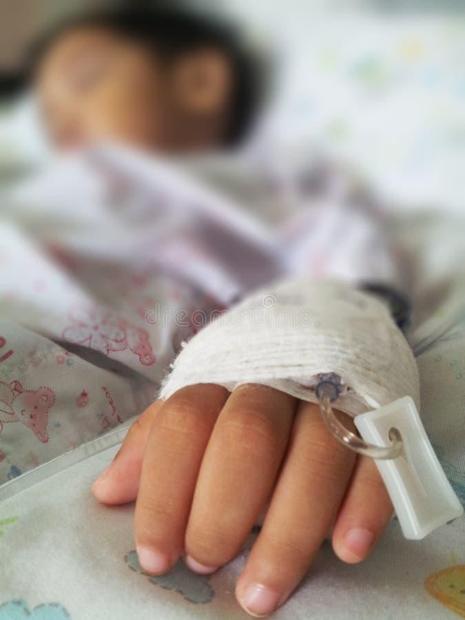 Kinderenpatiënt in het ziekenhuis met zout intraveneus, onduidelijk beeld en stock foto