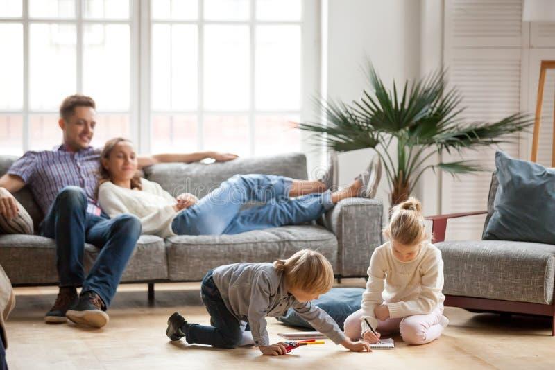 Kinderensiblings die het samentrekken spelen zich terwijl ouders relaxin stock fotografie