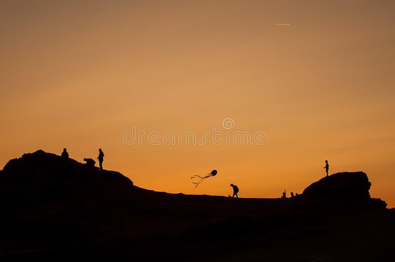 Kinderensilhouetten met vlieger die op zonsonderganglandschap vliegen met rotsen royalty-vrije stock fotografie