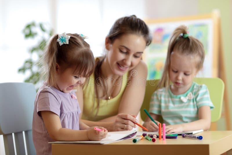 Kinderenstudenten met leraarstekening in kunstacademieklasse Moeder en jonge geitjes thuis De kinderen stellen tevreden royalty-vrije stock afbeelding