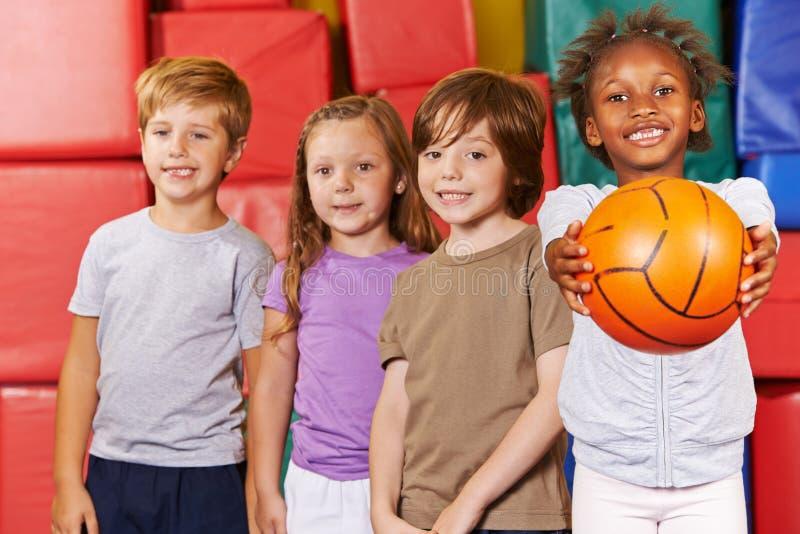Kinderenteam met basketbal in gymnastiek royalty-vrije stock foto's