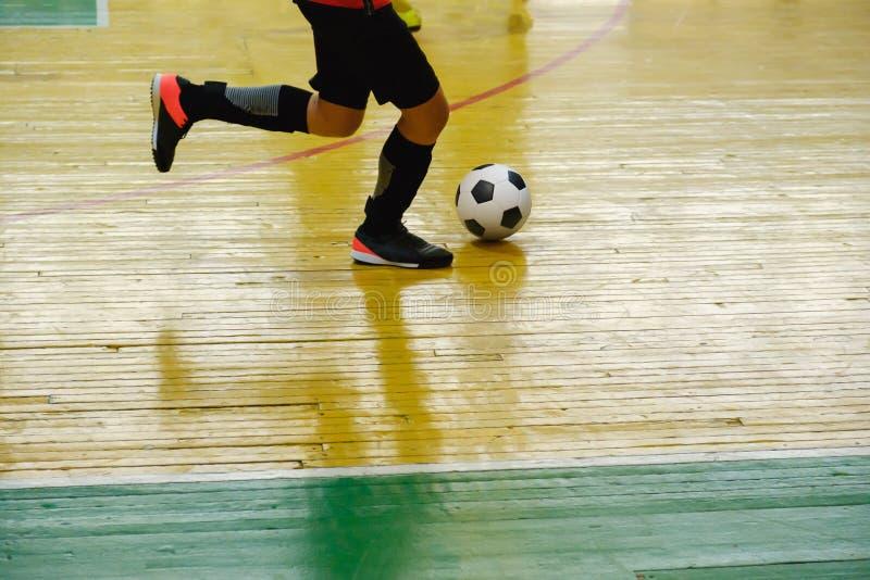 Kinderentiener de futsal binnengymnastiek van het opleidingsvoetbal Jonge jongen die met voetbalbal binnenvoetbal opleiden stock afbeelding
