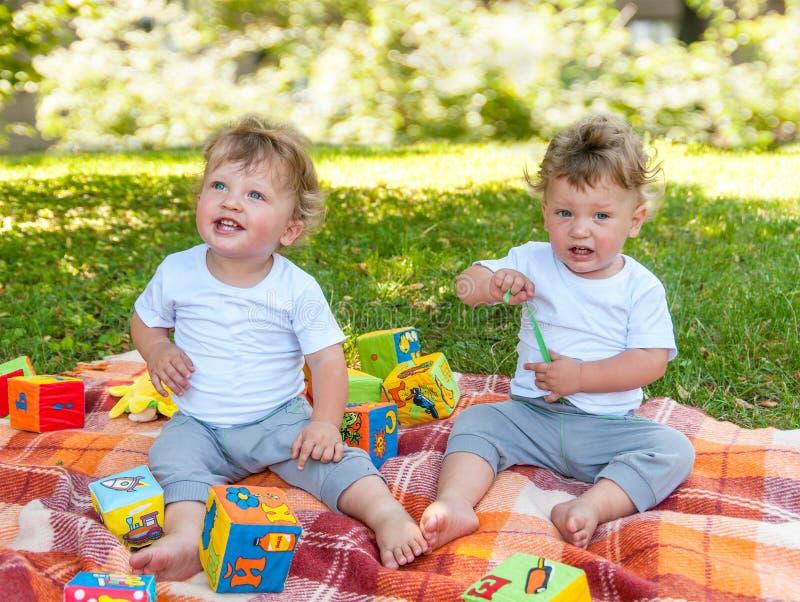 Kinderentweelingen die op een deken onder het speelgoed zitten stock afbeeldingen