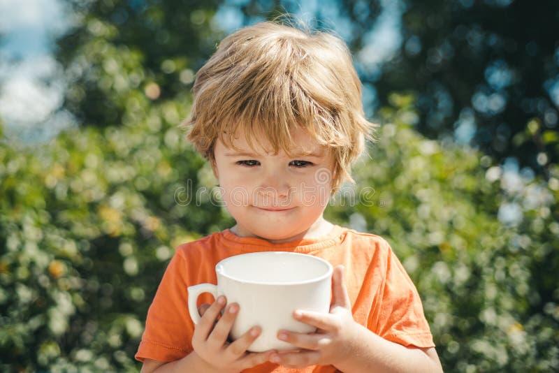 Kinderfeiertage auf Naturhintergrund Getränkmilch mit weißer Schale Nettes Kind stockbild