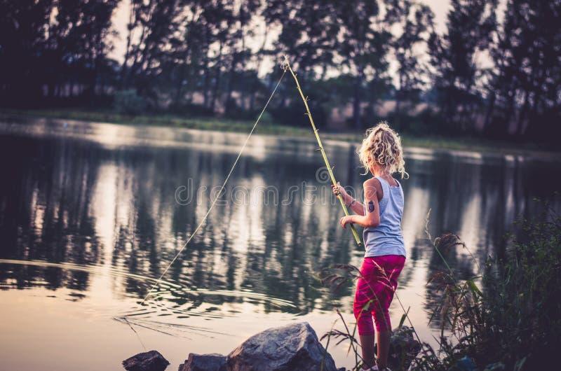 Kinderfischen auf dem See zur Sonnenuntergangzeit lizenzfreie stockbilder