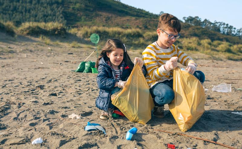 Kinderfreiwillige, die den Strand s?ubern lizenzfreies stockfoto