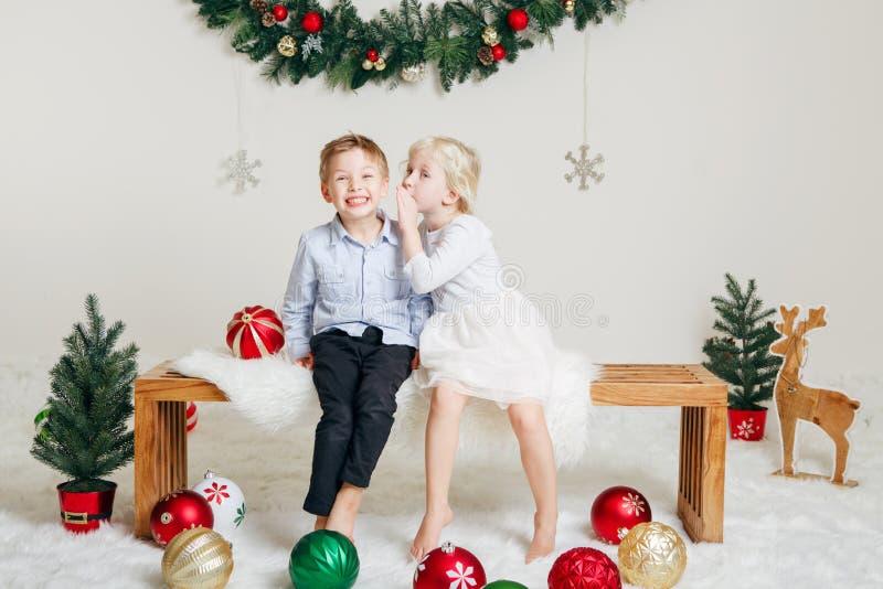 Kinderfreunde, die das Küssen sitzen zusammen, umarmend, Weihnachten oder neues Jahr feiernd stockbild