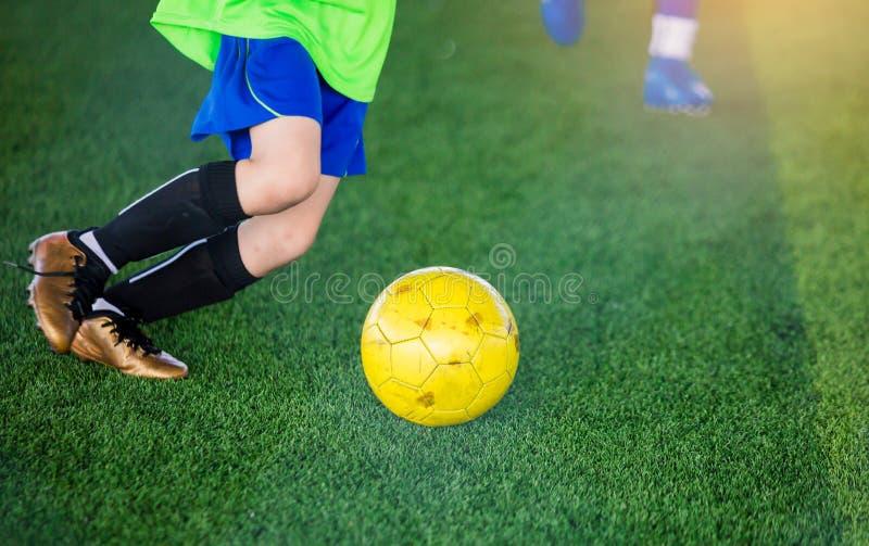 Kinderfußballspieler-Geschwindigkeitslauf, zum des Balls zum Ziel zu steuern und zu schießen lizenzfreie stockbilder
