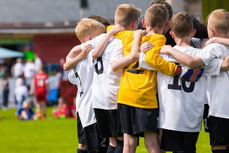 Kinderfußballteam Kinderfußball-Akademie Junge Fußball-Spieler in Jersey-Hemden, die zusammen auf der Neigung stehen lizenzfreies stockbild