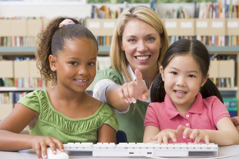 Kindergärtnerin, die mit Kindern sitzt lizenzfreie stockbilder