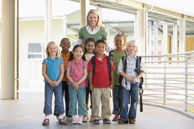 Kindergärtnerin, die mit Kindern steht lizenzfreie stockbilder