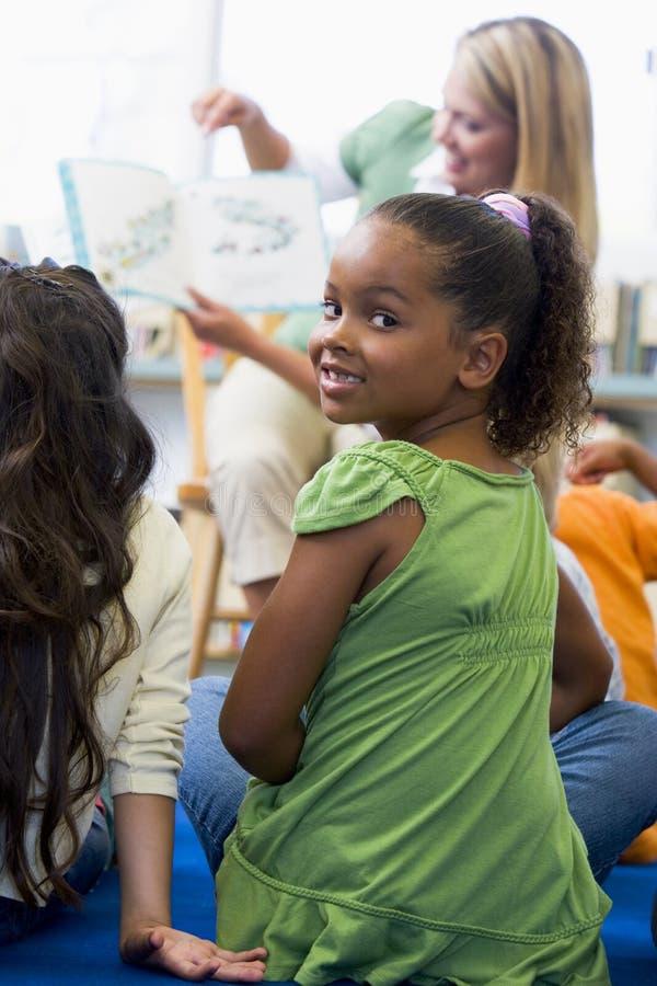Kindergärtnerin, die zu den Kindern liest stockfotografie
