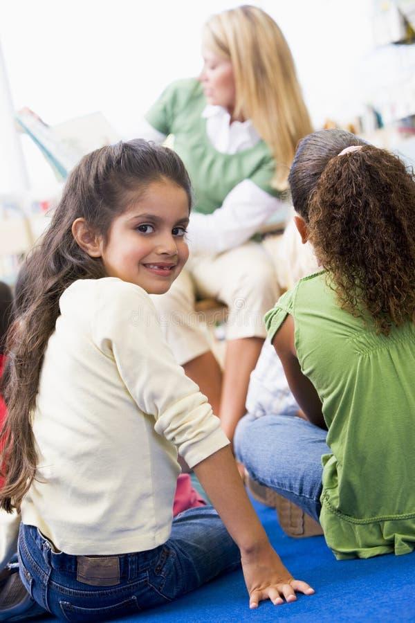 Kindergärtnerin, die zu den Kindern liest lizenzfreies stockbild