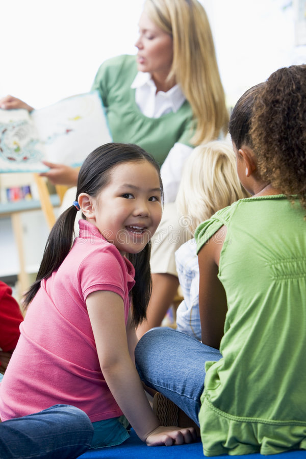 Kindergärtnerin, die zu den Kindern liest lizenzfreie stockfotos