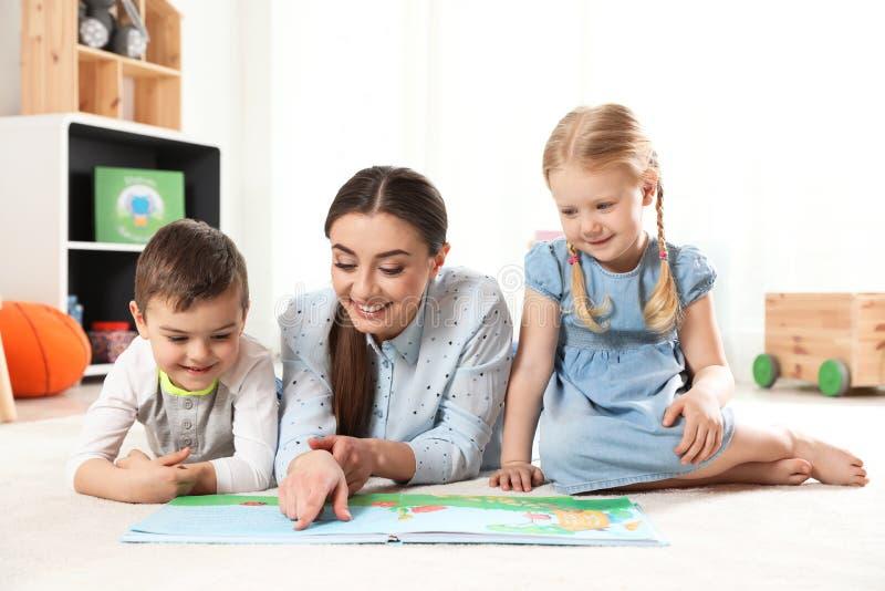 Kindergärtnerin-Lesebuch zu den Kindern Lernen und Spielen lizenzfreie stockfotos