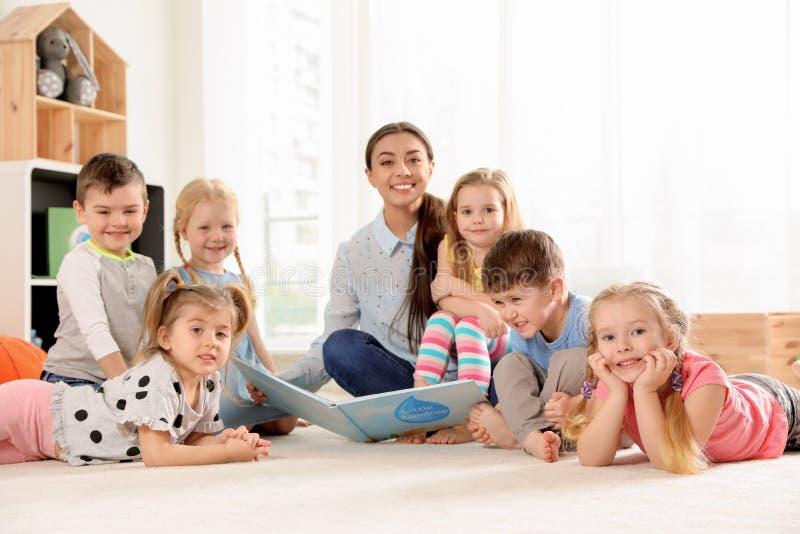 Kindergärtnerin-Lesebuch zu den Kindern zuhause stockfotos