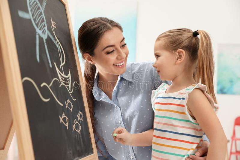 Kindergärtnerin und kleines Kind nahe Tafel Lernen und Spielen lizenzfreies stockfoto