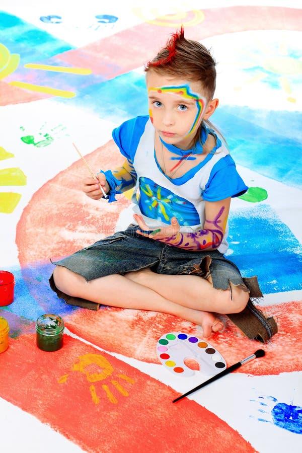 Kindergarten. Portrait of a beautiful child enjoying his painting. Education stock photo