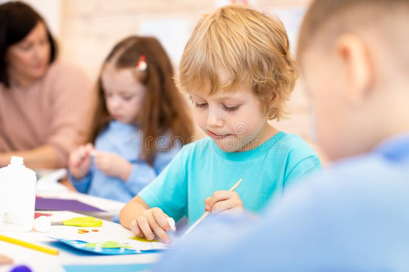 Kindergarten children doing arts and crafts with teacher in day care centre stock photography