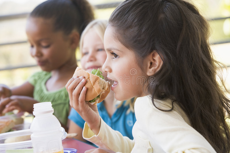 Kindergarten children eating lunch stock image
