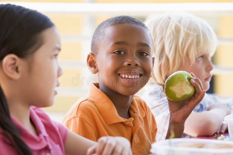 Kindergarten children eating lunch royalty free stock photos