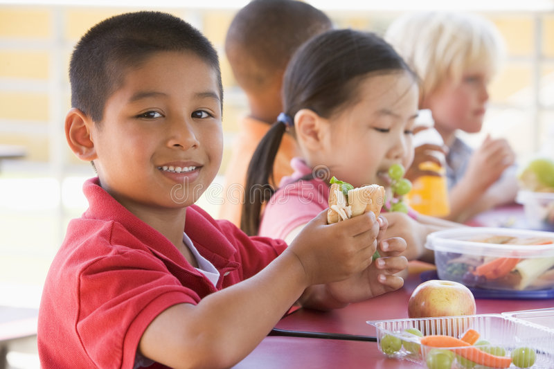 Kindergarten children eating lunch stock photos