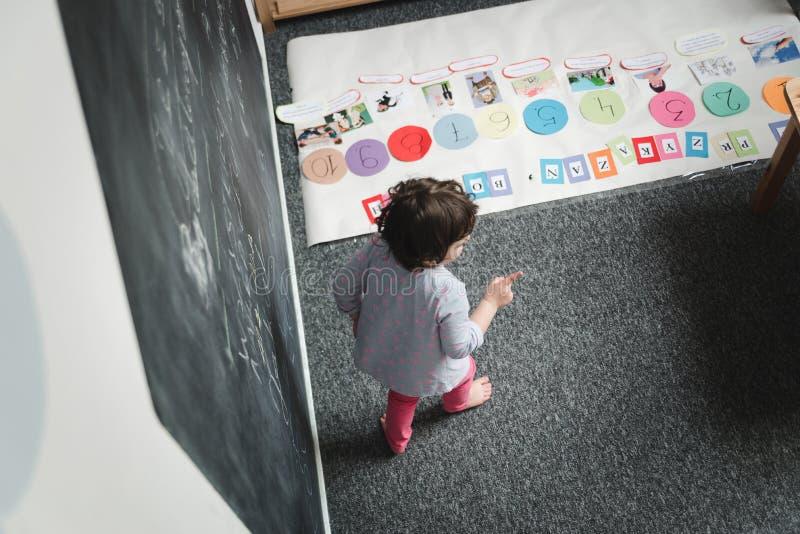 Kindergarten-Konzept Glückliche Vorschulmädchenzeichnung auf Tafel und haben Spaß stockbild
