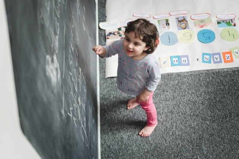 Kindergarten-Konzept Gl?ckliche Vorschulm?dchenzeichnung auf Tafel und haben Spa? stockfotografie