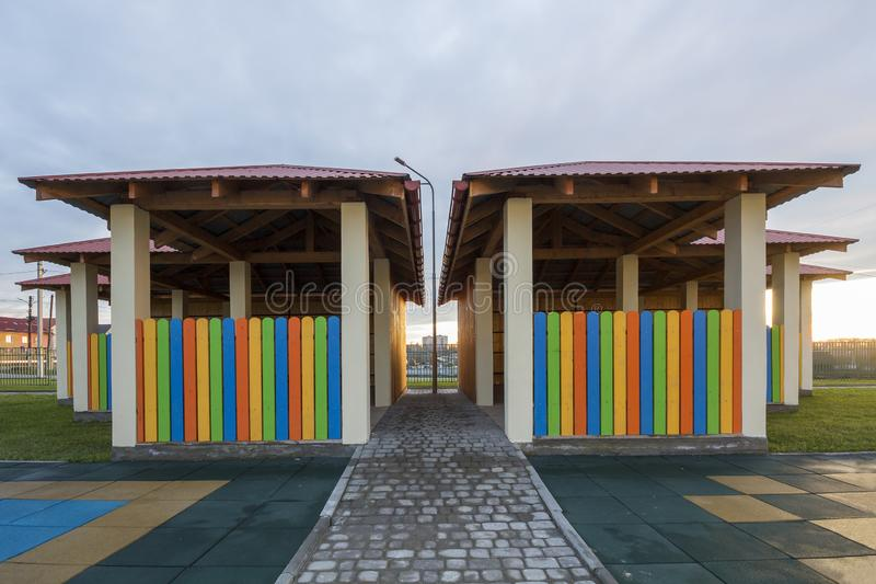 Kindergarten playground with bright new alcove with multicolored low fence, big yard with soft rubber flooring on blue sky copy. Space background. Perfect place royalty free stock photography