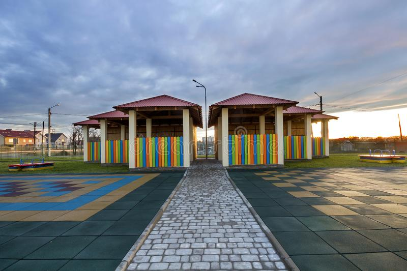 Kindergarten playground with bright new alcove with multicolored low fence, big yard with soft rubber flooring on blue sky copy. Space background. Perfect place stock photography