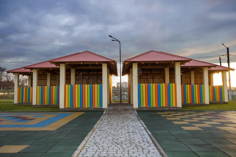 Kindergarten playground with bright new alcove with multicolored low fence, big yard with soft rubber flooring on blue sky copy. Space background. Perfect place stock image