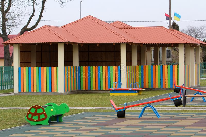 Kindergarten playground with bright new alcove with multicolored low fence, funny bench and seesaw swing in big yard with soft. Rubber flooring on sunny day stock photos