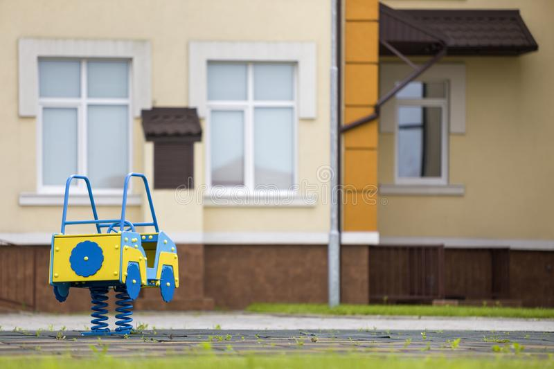 Kindergarten playground with bright toy car on spring. Children activities and recreation outdoors.  royalty free stock images