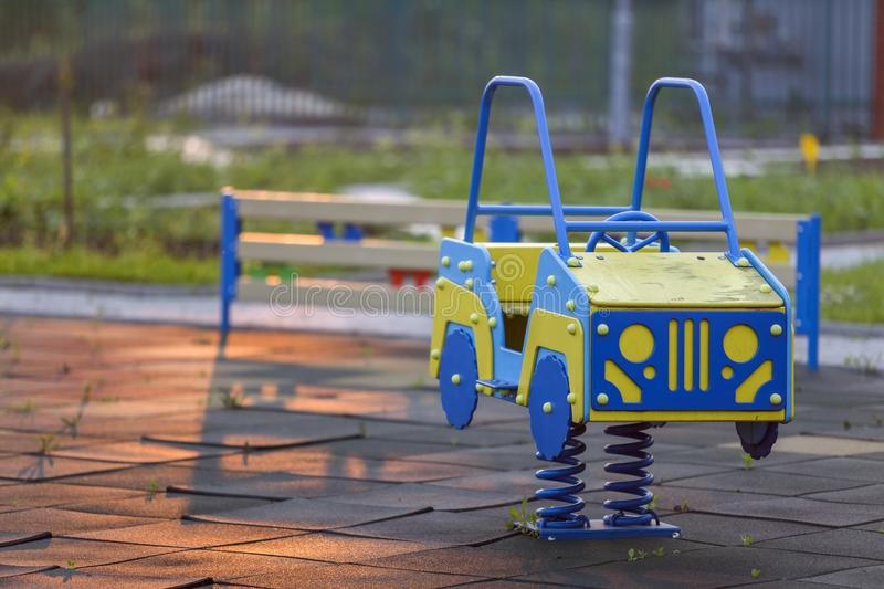 Kindergarten playground with bright toy car on spring. Children activities and recreation outdoors.  stock images