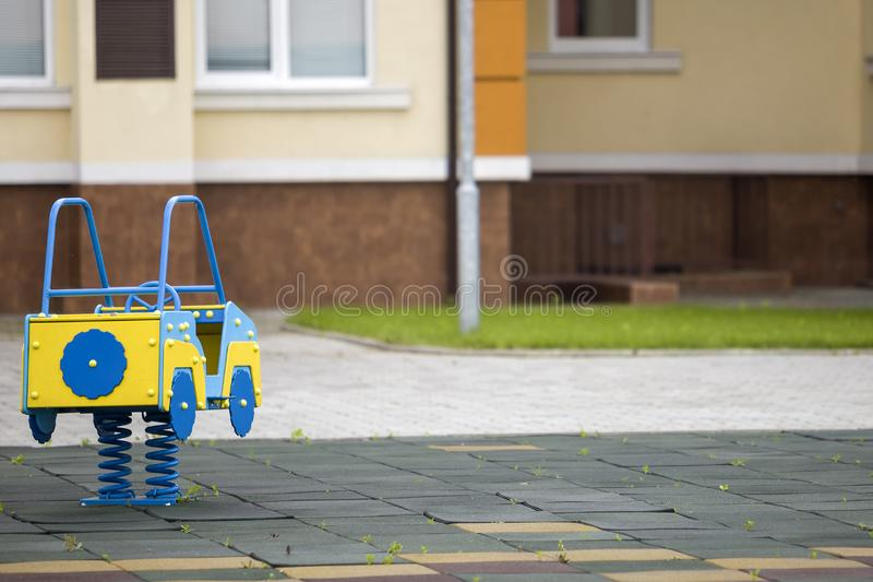 Kindergarten playground with bright toy car on spring. Children activities and recreation outdoors.  stock image