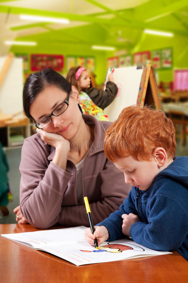 Kindergarten preschool teacher helping children. Kindergarten preschool teacher helping child student in classroom stock image
