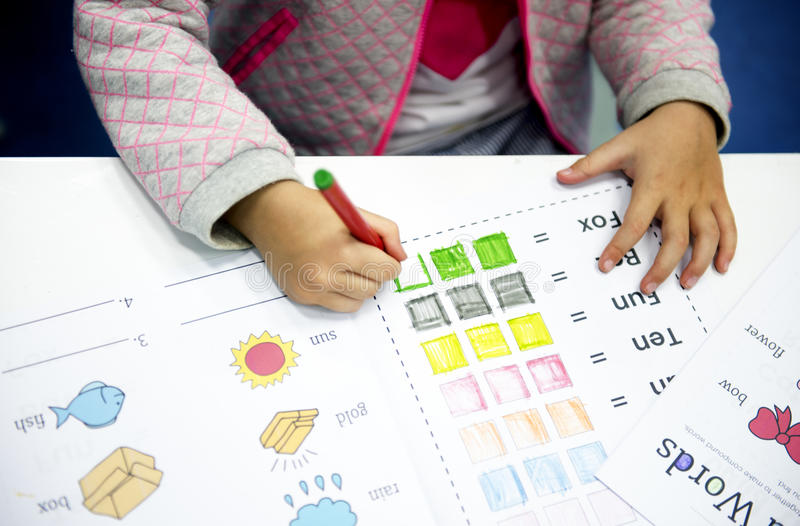 Kindergarten student coloring workbook in class stock photos