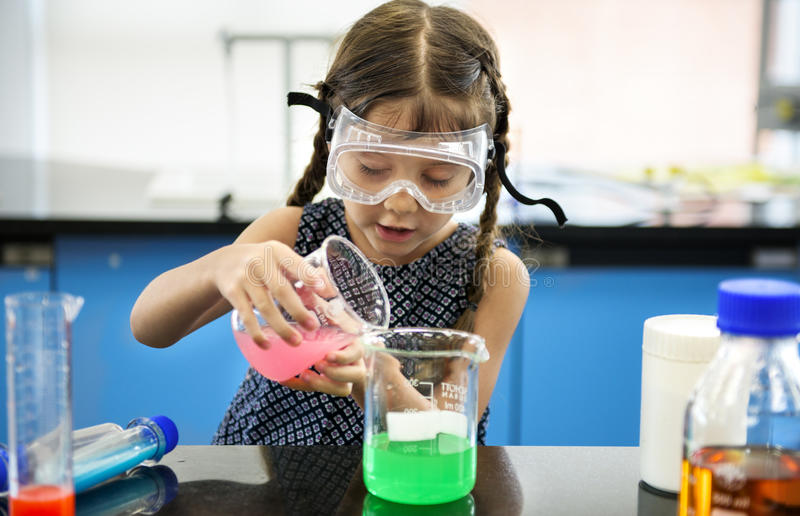 Kindergarten-Student Mixing Solution in der Wissenschafts-Experiment-Arbeit stockfotos