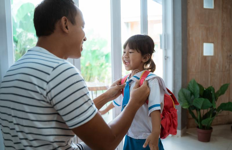 Kindergarten student wearing school uniform helped by her father royalty free stock images