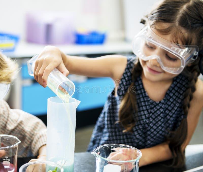 Kindergarten-Studenten, die Lösung im Wissenschafts-Experiment Labo mischen stockfoto