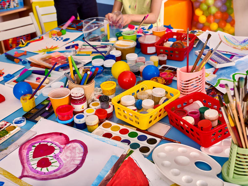 Kindergarten tables and chairs in interior decoration shelves for toys. Kindergarten tables with painting brush and teacher in interior . Preschool class royalty free stock photo
