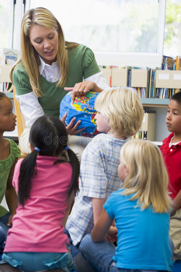 Kindergarten teacher and children looking at globe royalty free stock image