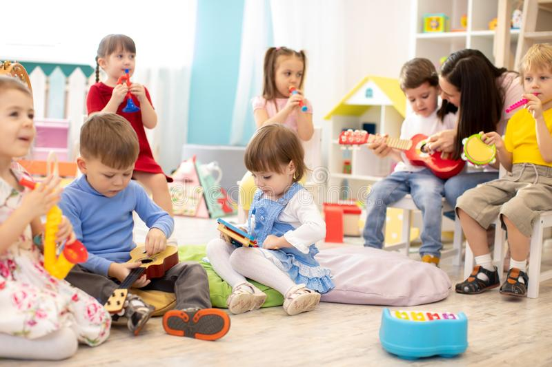 Kindergarten teacher with children on music lesson in daycare. Little kids toddlers play together with musical toys. royalty free stock photos