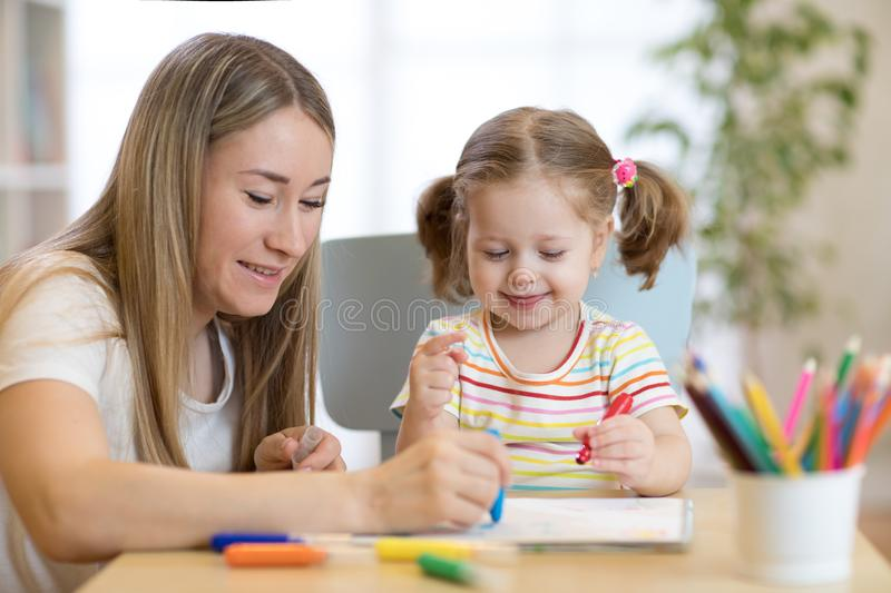 Kindergarten teacher and child girl drawing lessons at school stock photography