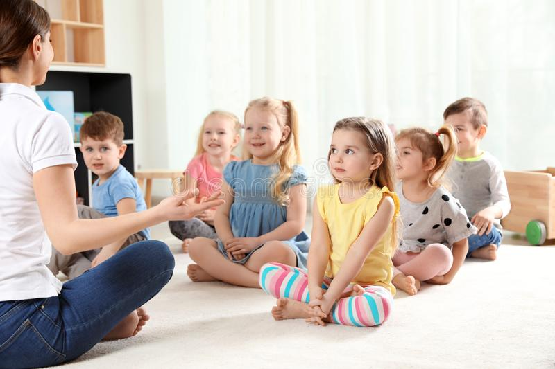 Kindergarten teacher and little children. Learning and playing stock photos